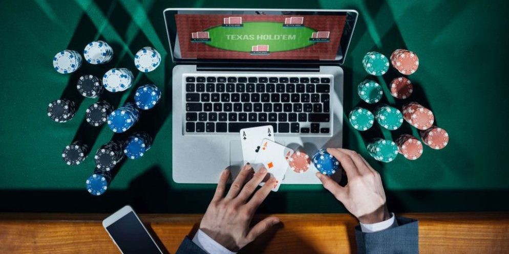 Laptop With Texas Hold'Em On Screen And Man Holding Playing Cards With Casino Chips