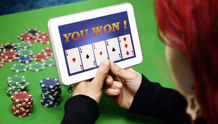 Woman Holding Tablet With You Won Screen And Casino Chips On A Table Below