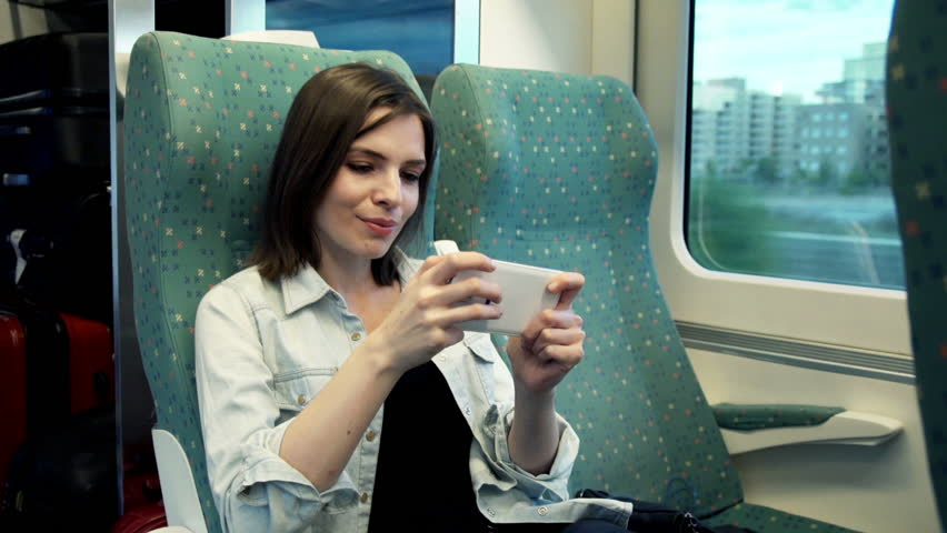 woman gambling on mobile in a train