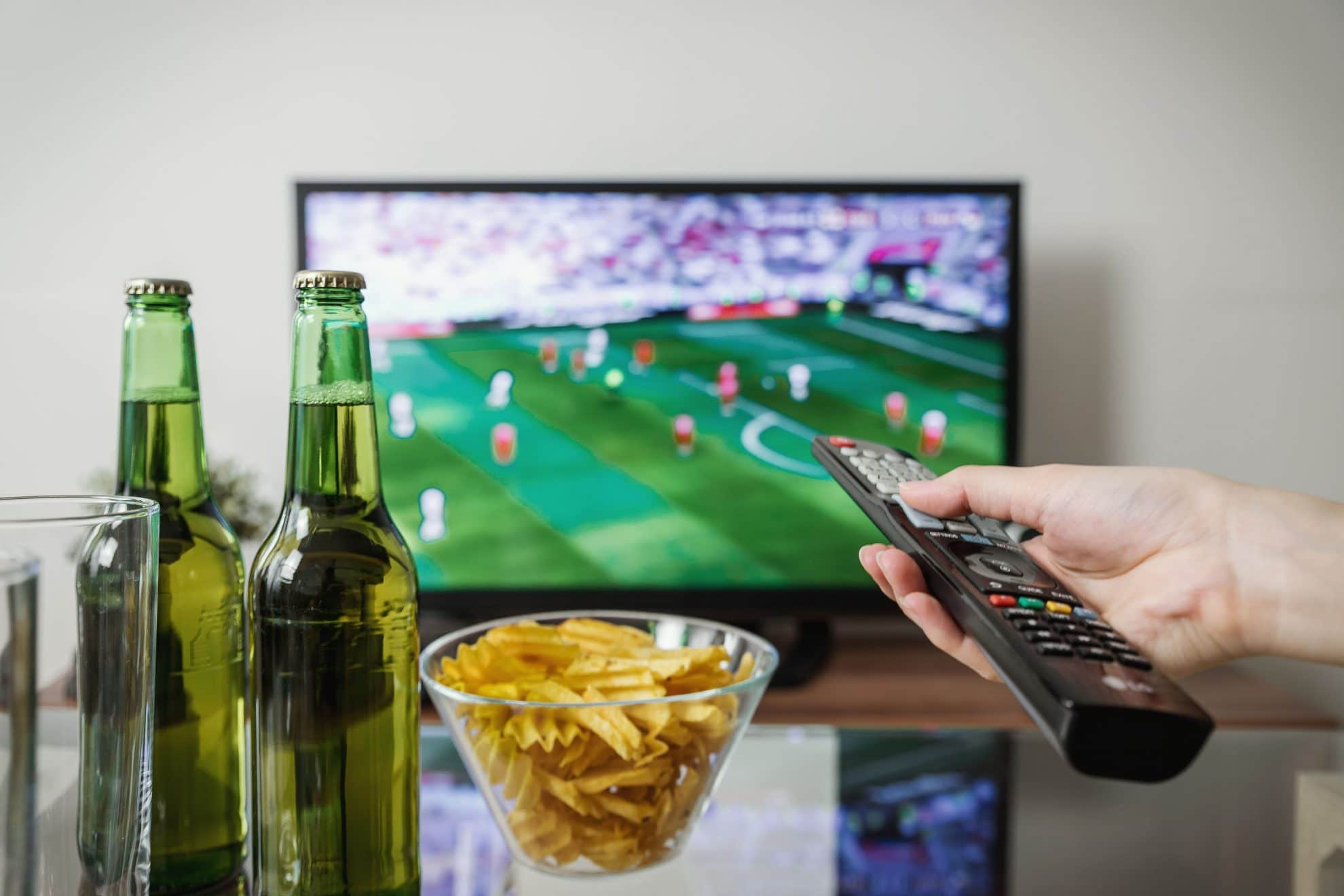 TV Bottles Of Beer Crisps And Man Holding Remote Control