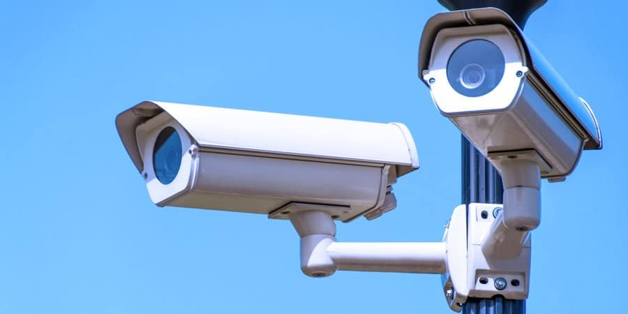 photo of security cameras against blue sky